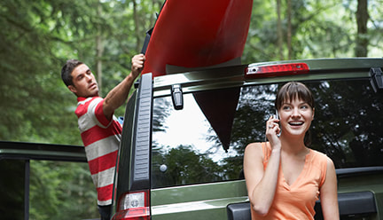 A guy loading a kayak on top of an SUV and a girl talking on her mobile phone